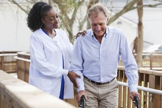 Nurse helping senior man with walker
