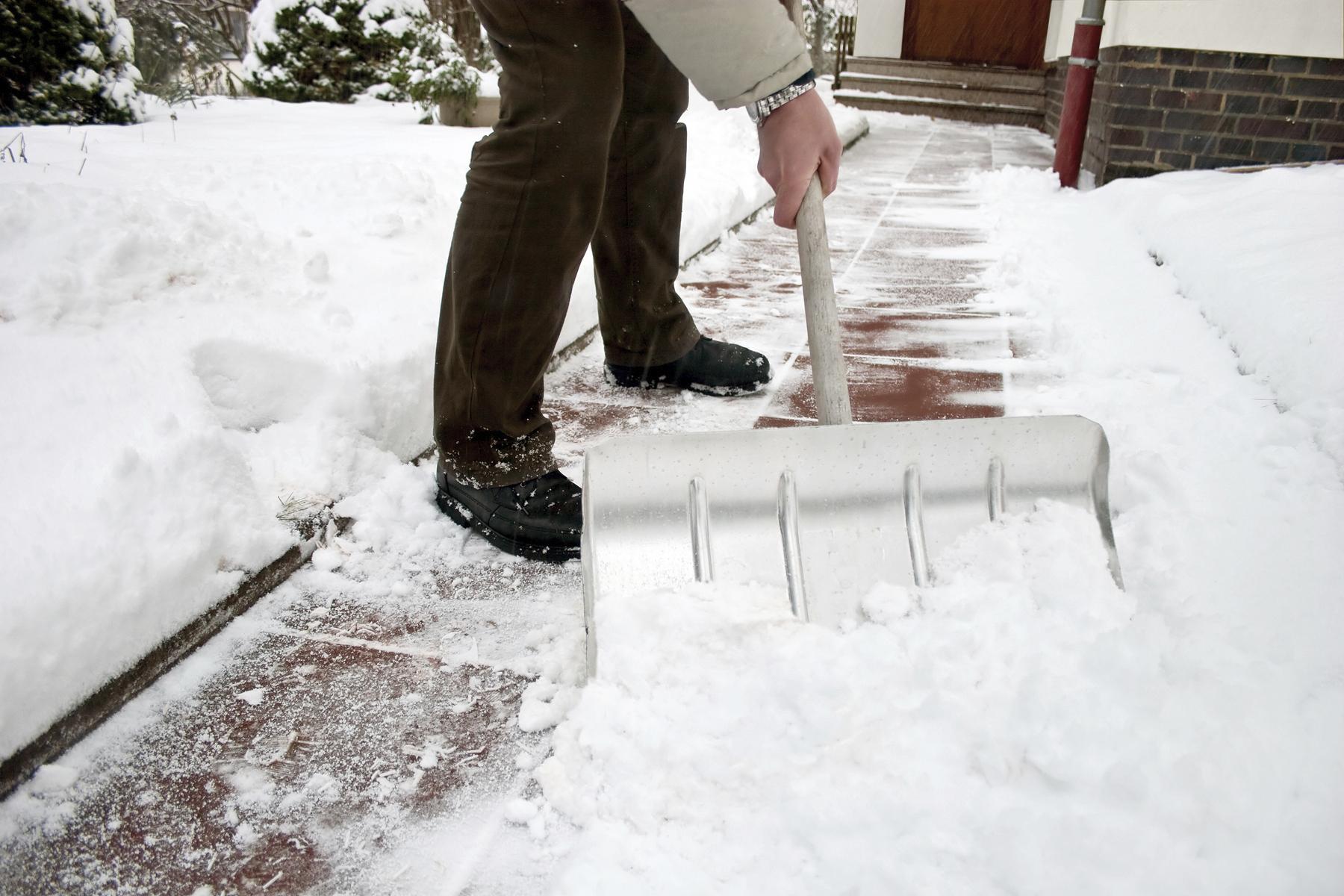 Man shoveling snow at a footpath